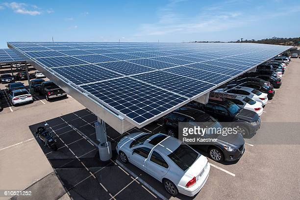 Solar panels mounted above a parking area supply electricity for a business and shade for the cars below.