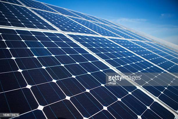 solar panels on a sunny day against clear blue sky - solar panels stock photos and pictures