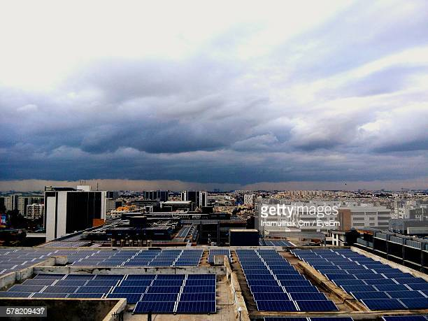 Solar Panels On Building Terrace Against Sky In City