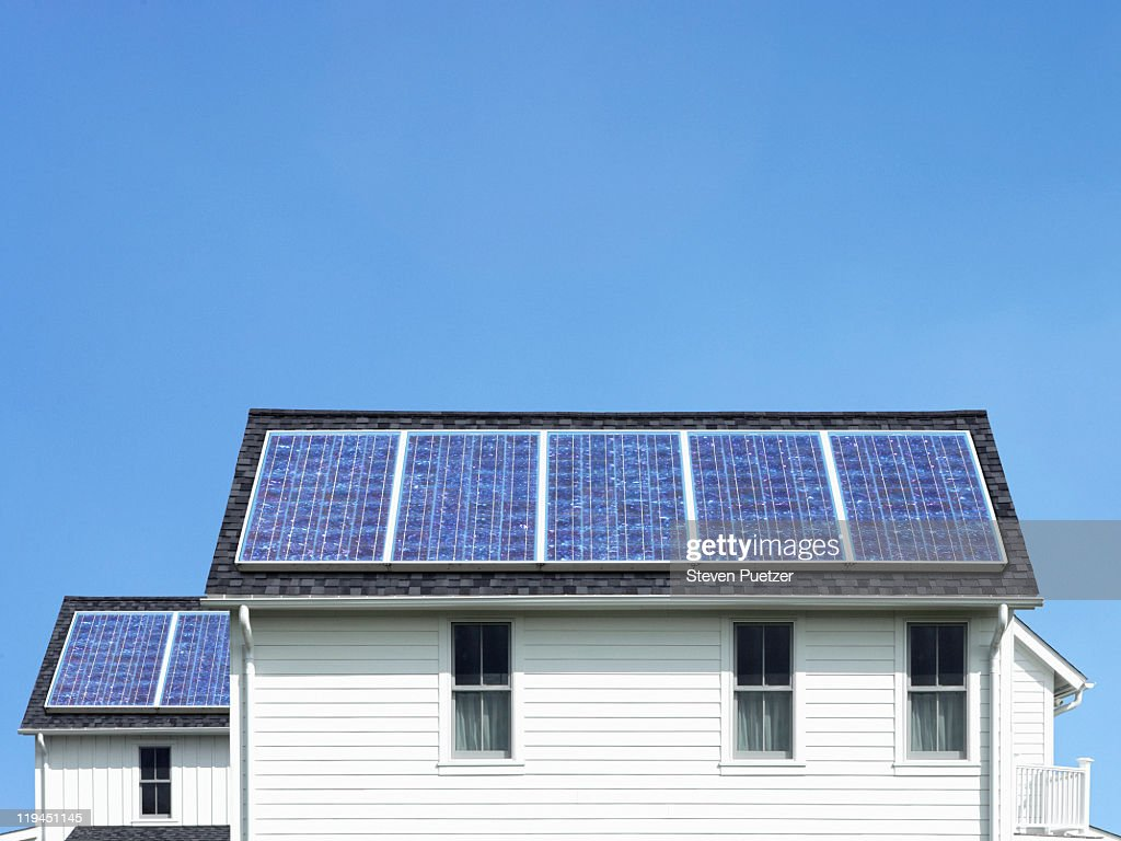 Solar panels on roof of white house : Stock Photo