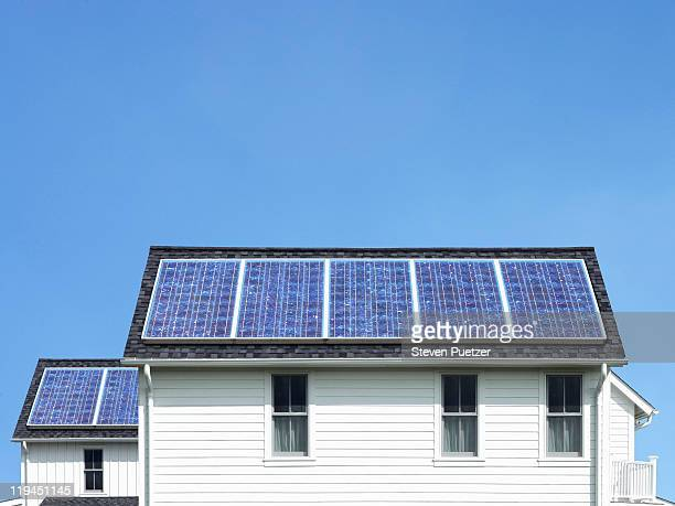 solar panels on roof of white house - solar panel stock pictures, royalty-free photos & images