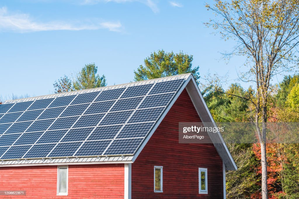 Solar panels on the roof of a farm building on a clear autumn day : Stock Photo