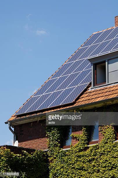 Painéis solares no telhado de casa coberto de Hera