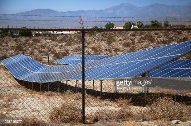 solar panels seen through a chain link fence as they follow the contour of sloping ground; houses, mountains and blue sky beyond - timothy hearsum imagens e fotografias de stock