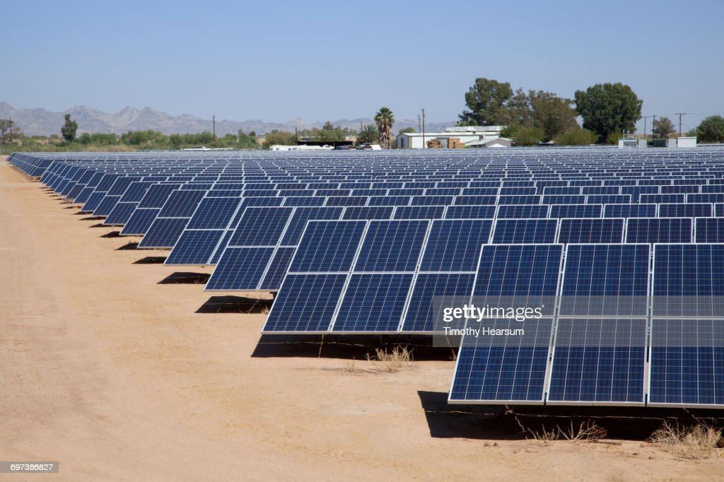 Solar panels with farm buildings, mountains beyond : Stock Photo