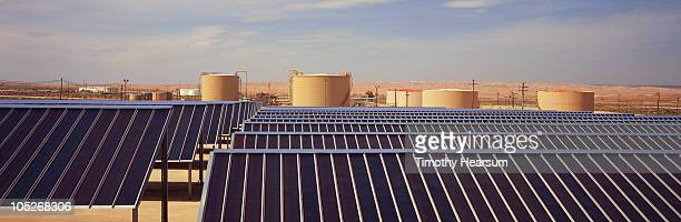 solar panels with oil storage tanks beyond - timothy hearsum stock pictures, royalty-free photos & images