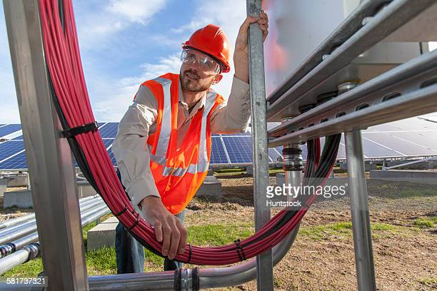 Solar photovoltaic installer working on power connections for a PV array