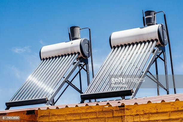 Solar power geysers to heat hot water sit on the roof of a residential shack in the Alexandra township outside Johannesburg South Africa on Thursday...