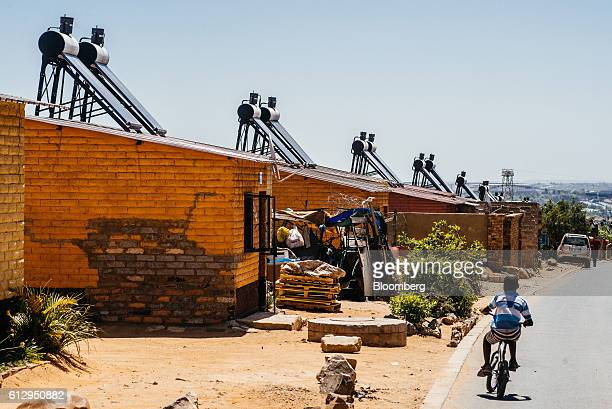 Solar power geysers to heat hot water sit on the roofs of residential shack in the Alexandra township outside Johannesburg South Africa on Thursday...