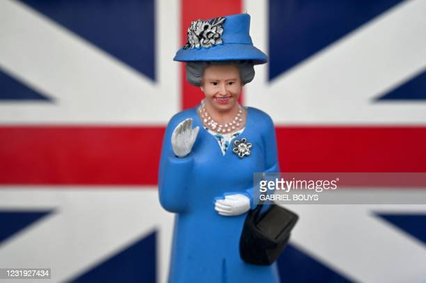 Solar powered miniature figurine of waving Queen Elizabeth II is pictured in the window of a souvenir shop in Madrid on March 25, 2021.