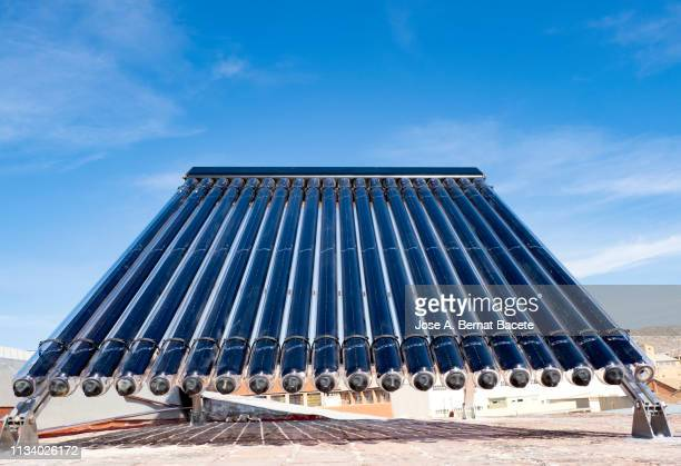 solar water panel heating on a roof. - solar mirror stock pictures, royalty-free photos & images