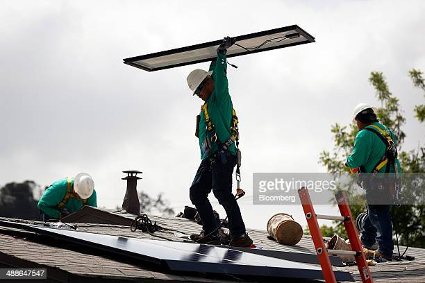 A SolarCity Corp employee carries a solar panel being installed on the roof of a home in the Eagle Rock neighborhood of Los Angeles California US on...