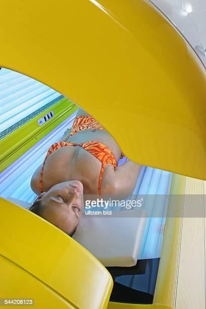 Solarium: Frau liegt auf einer Sonnenbank-