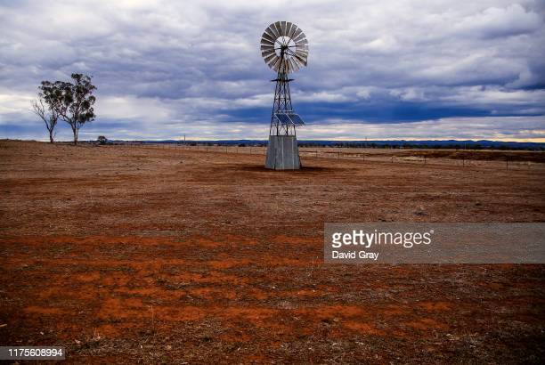 Solar-powered windmill stands in a drought-affected paddock as rain clouds move overhead on September 18, 2019 on the outskirts of Dubbo, Australia....