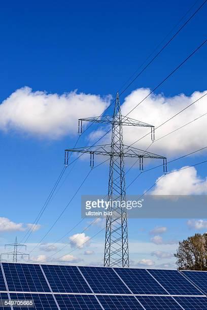Solarzellen zur Gewinnung von alternativer Sonnenenergie Im Hintergrund ein Strommast