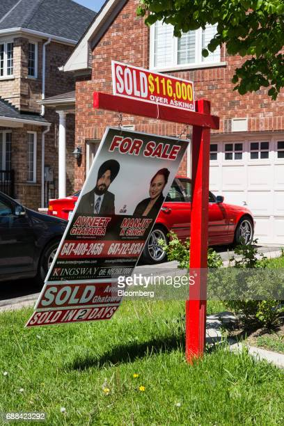 A 'Sold $116000 Over Asking' sign is displayed outside of a house in Brampton Ontario Canada on Saturday May 20 2017 After a double whammy...
