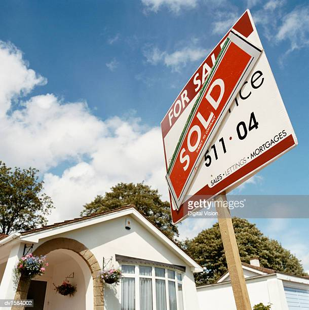 sold sign in front of a bungalow - sold single word stock pictures, royalty-free photos & images