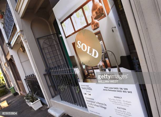 A sold sign on a real estate board advertising residential property is seen in front of a house in Sydney on August 1 2017 Australia's central bank...