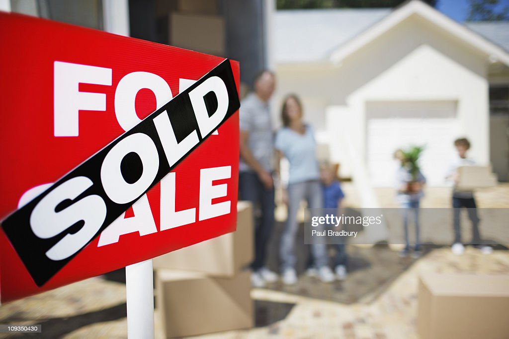 Sold sign on house with family in the background : Stock Photo
