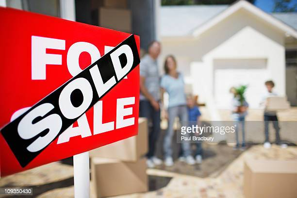 sold sign on house with family in the background - vendor stock pictures, royalty-free photos & images