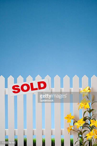 Sold Sign On White Picket Fence