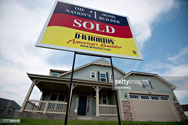 A sold sign stands outside a new home in the DR Horton Inc Cambridge at Southbury development in Oswego Illinois US on Tuesday Aug 20 2013 The...