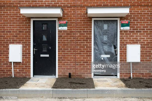Sold signs sit on the wall outside newly built homes at a Persimmon Plc residential construction site in Grays UK on Tuesday Aug 14 2018 Persimmon...