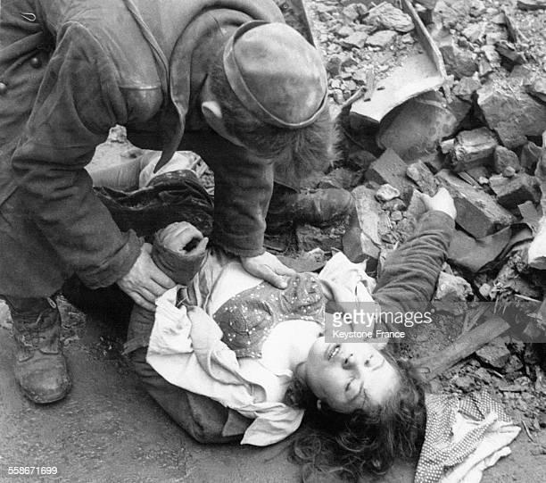 Soldat russe tout juste libéré par les Anglais prodiguant les premiers secours à une jeune fille atteinte d'une balle de fusil dans un camp près de...