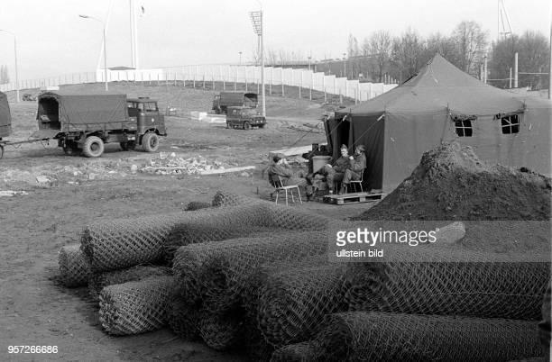 Soldaten der DDRGrenztruppen sitzen im Grenzgebiet an der Eberswalder Straße in Berlin vor ihrem Zelt aufgenommen am Die ersten Grenzzäune sind schon...