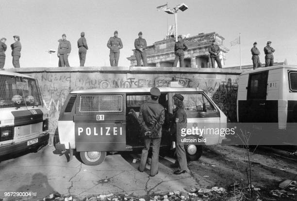 Soldaten der DDRGrenztruppen stehen auf Westberliner Polizisten vor der Berliner Mauer am Brandenburger Tor aufgenommen am in Berlin Zwei Tage später...