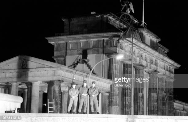 Soldaten der DDRGrenztruppen stehen in der Nacht zum auf der Panzermauer am Brandenburger Tor in Berlin und verfolgen die nächtlichen Vorbereitungen...