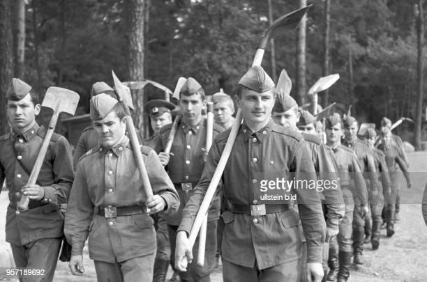 Soldaten der in der Umgebung von Cottbus stationierten sowjetischen und deutschen Militäreinheiten marschieren mit Schaufeln und Spaten am Madlower...
