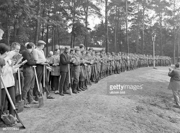 Soldaten der in der Umgebung von Cottbus stationierten sowjetischen und deutschen Militäreinheiten stehen mit Schaufeln und Spaten am Strandufer des...