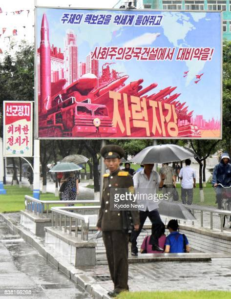 A solder stands in front of a sign board depicting North Korea's missile and nuclear power in Pyongyang on Aug 24 a day before the Day of Songun a...