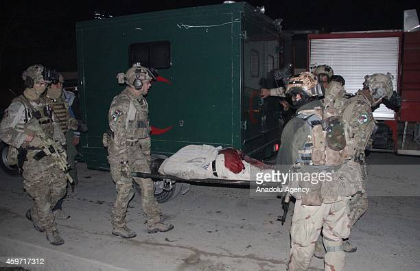 US solders carry body of a foreigner after a Taliban attack on foreign aid workers' guest house in Kabul November 29 2014 A group of Taliban...