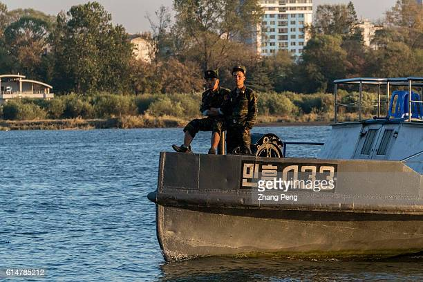 Solders on a tour boat sailing on Yalu River at North Korea side of border. Sinuiju, facing Chinese Dandong across the international border of the...