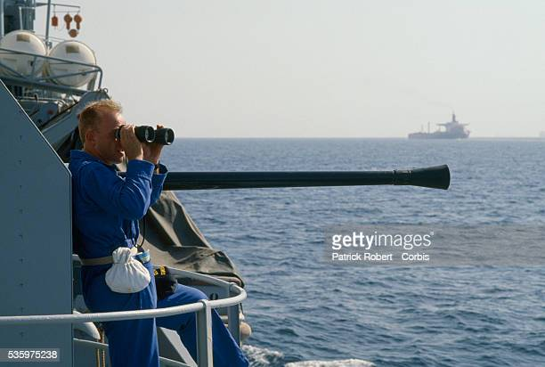 A soldier aboard the French gunboat Doudart de Lagree scans the horizon with binoculars while patrolling the Persian Gulf during the IranIraq War...