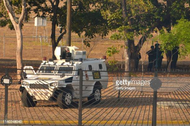A soldier aims a machinegun in a vehicle of Guardia Nacional Bolivariana and another group stand guard close to air force base La Carlota on April 30...