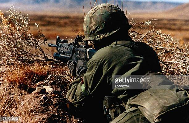Soldier aims rifle with grenade launcher