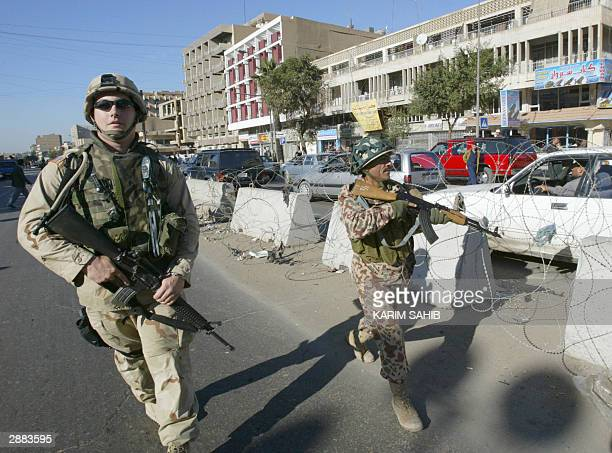 Soldier and a member of the Iraqi Civil Defense Corps conduct a joint patrol in central Baghdad 20 January 2004. In the northern city of Mosul,...