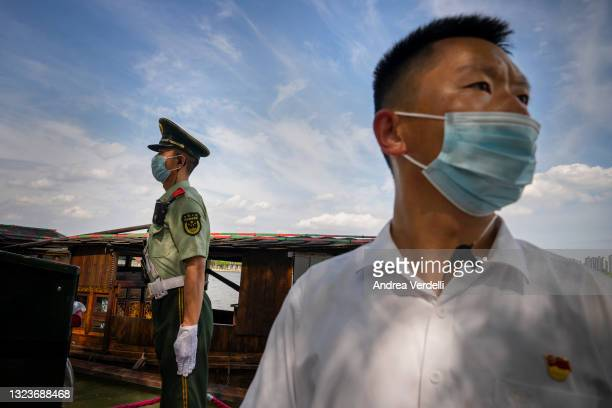 Soldier and a security guard stand by the Red Boat, a replica of the original vessel, on June 15 at Nanhu Lake, Jiaxing, Zhejiang Province, China,...