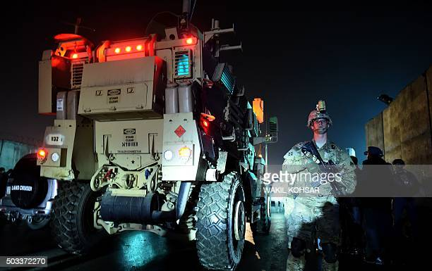 A US soldier and Afghan security forces stand next a military vehicle as they arrive at the site of a suicide car bomb attack that targeted a...