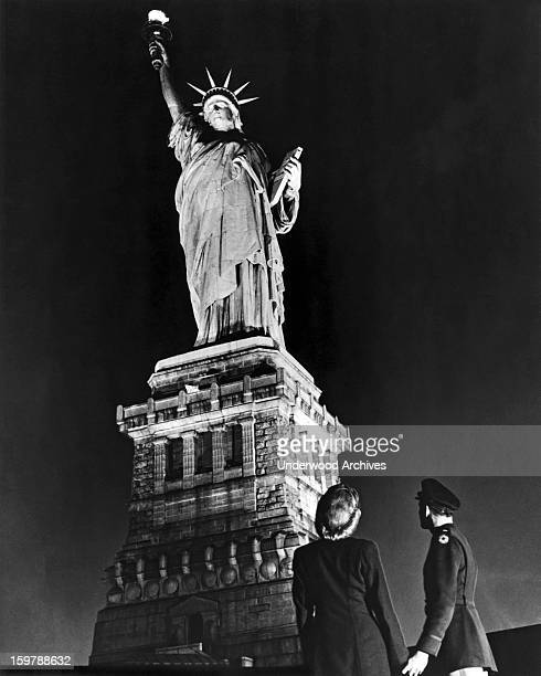A soldier and his companion gaze up on VE Day at the Statue of Liberty after it was illuminated except for a brief period on DDay for the first time...