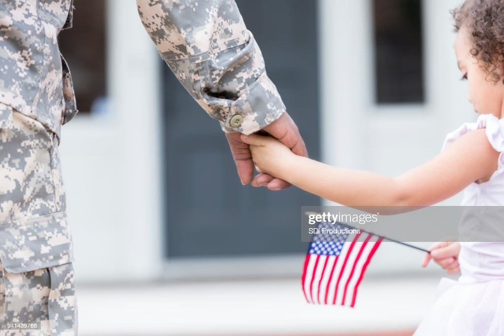 Soldier and his daughter walk hand in hand : Stock Photo