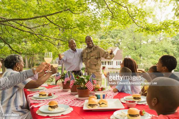 Soldier and multi-generation family toasting with lemonade at picnic