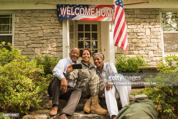 Soldier and parents sitting on front stoop posing for cell phone selfie