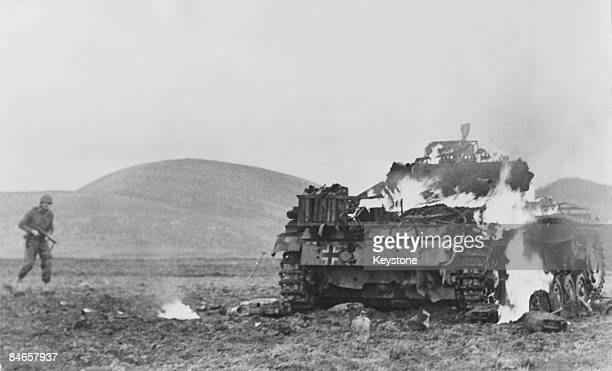 A US soldier approaches a burning German tank blasted by Allied antitank units in Tunisia during World War II circa 1943