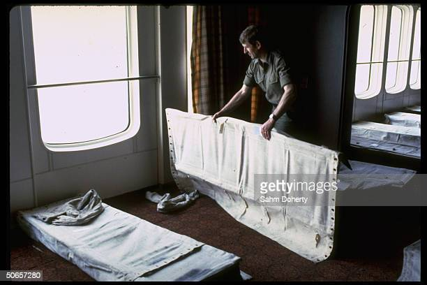 Soldier arranging cots installed in casino on QE2 before troops set sail for Falklands