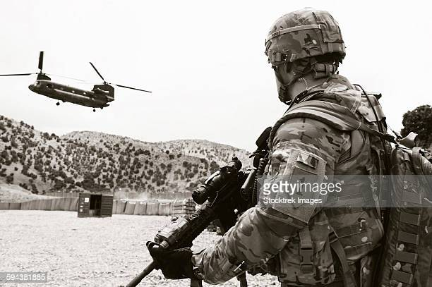 soldier assigned to the 1st infantry division awaits an incoming ch-47 chinook helicopter. - us military emblems stock pictures, royalty-free photos & images