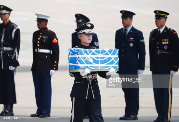 A soldier carries a casket containing a remain of a US soldier who were killed in the Korean War during a ceremony at Osan Air Base on July 27 2018...